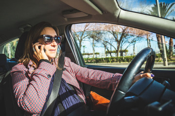 Woman driving and talking on cell phone at the same time. Girl in car talking on mobile phone putting people's lives in danger