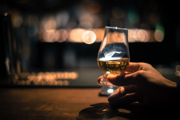 Foto op Canvas Alcohol Hand holding a Glencairn single malt whisky glass