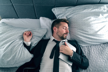 Overworked businessman in suit sleeping and lying on the bed and holding tablet on his chest.