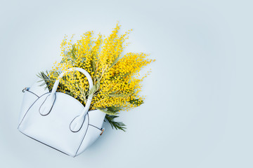 Wall Mural - A bouquet of yellow flowers in a women's handbag.