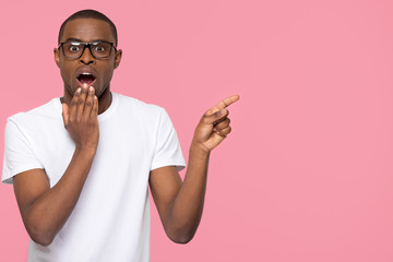 Shocked black man with open mouth pointing at copy space stunned advertising unbelievable sale, astonished amazed african guy with surprised face looking at camera isolated on pink studio background