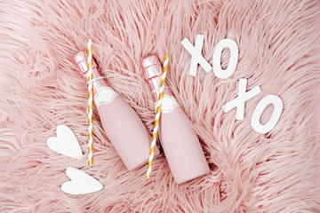 Champagne bottles on pink fluffy fur background. Flat lay, top view
