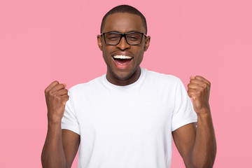 Excited overjoyed lucky black man feeling winner screaming with joy looking at camera isolated on pink studio background, african guy celebrating win triumph rejoicing victory motivated by success