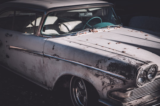 Front side view of a worn and beat up classic American car from the fifties