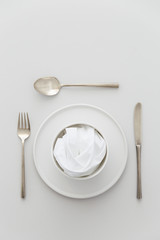Minimal grey and white table setting with a brass cutlery set, a plate and a bowl with a white napkin.