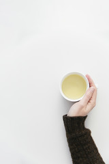 Women's hand in a brown warm knitted sweater holding a white mug with hot herbal tea.