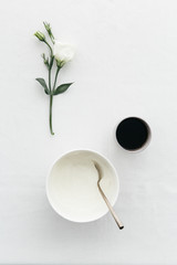 Breakfast table with Greek yoghurt, black coffee and white flower.