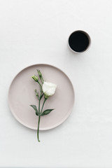 White flower on a plate with a cup of black coffee.