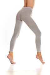 sexy slim female buttocks and legs in gray leggingss on white background