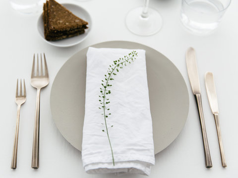 A dinner table with bread and cream cheese for starter, white wine and water to drink.