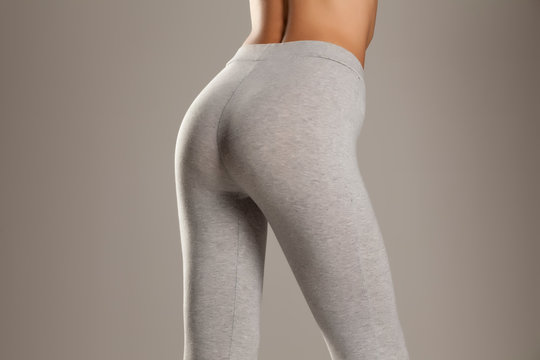 sexy slim female buttocks in gray leggingss on gray background