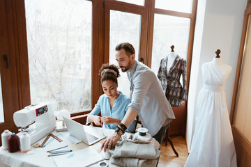 Wall Mural - From paper to laptop. Man and woman at design studio