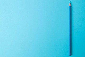 Composition with a blue pencil on a bright trend blue background. view from above. space for text