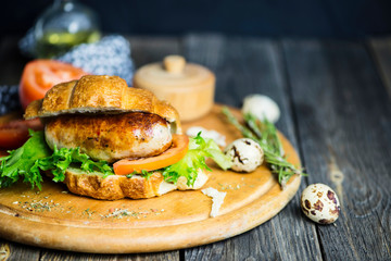 grilled pork sausage sandwich with spices on old wooden background