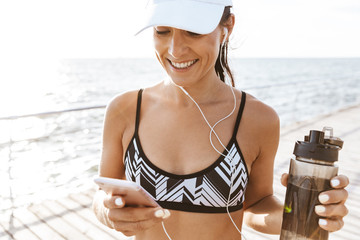 Beautiful young sports fitness woman using mobile phone drinking water at the beach outdoors listening music with earphones.
