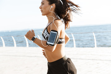 Young sports fitness woman running at the beach outdoors.