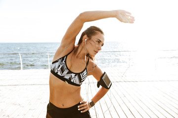 Beautiful young sports fitness woman make stretching exercises at the beach outdoors listening music with earphones.