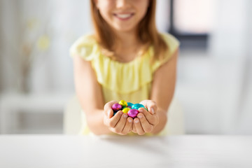 easter, holidays and people concept - close up of happy girl holding chocolate eggs in colorful foil wrappers