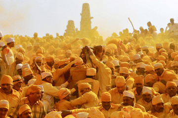 Devotees throw turmeric powder as an offering to the shepherd god Khandoba as others carry a palanquin during 'Somvati Amavasya' at a temple in Jejuri