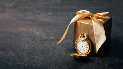 Gold pocket watch and craft paper gift with ribbon on dark background. Wedding, elegant, Love, romance, Valentines day concept.
