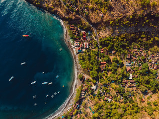 Aerial view of village with blue sea and boats, drone shot in Bali.