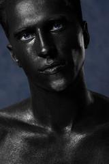 a man in black make-up. portrait in dark paint. Art photography portrait