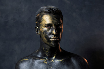 a man in black make-up with gold. portrait of a guy in dark paint with gold. Artistic portrait photography