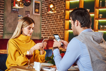 Always with smartphone. Young couple are sitting in restaurant with smartphones