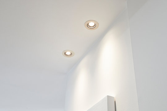 Two spot light illuminated on white ceiling