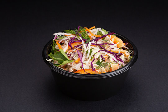 mix vegetables salad with purple cabbage, white cabbage, lettuce, carrot in dark clay bowl on black background.