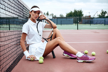 Ready to play? Young tennis player sits on a court and holds a racket