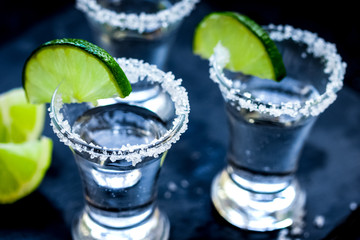 Set for tequila party with lime and salt on black background
