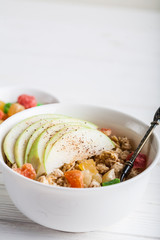 Breakfast bowl of oat granola with apple and dry fruit in a white bowl on white wooden background  with a yogurt. Copy space