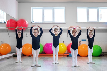 Little kids dance in dance class. The concept of sport, education, childhood, hobbies and dance.