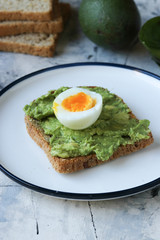 Toast with avocado and egg, bread slice with avocado and egg