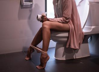 Woman using toilet.