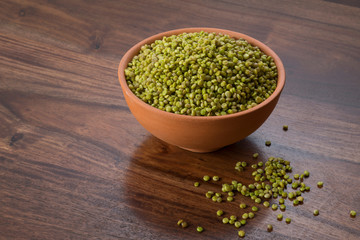 Front  View of Fresh Green Tender Sorghum in a Earthen Bowl on Wooden Background