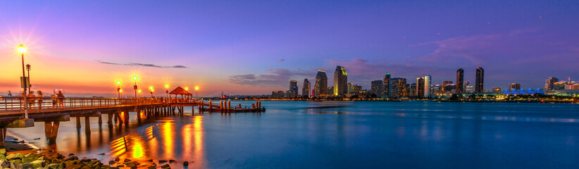 Panorama of Coronado old pier reflecting on in San Diego Bay from Coronado Island, California, USA. San Diego cityscape skyline with Downtown and Waterfront Marina District at twilight on background. Fototapete