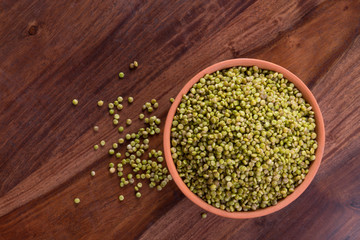 Top View of Fresh Green Tender Sorghum in a Earthen Bowl on Wooden Background