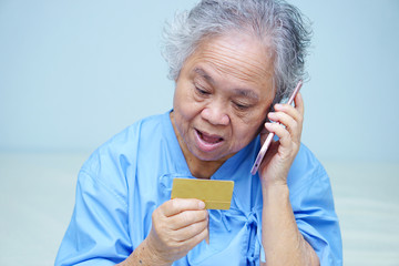 Asian senior or elderly old lady woman patient with credit card talking on the mobile phone while sitting and happy on bed in nursing hospital ward : healthy strong medical concept