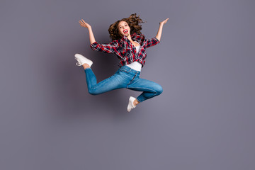 Full length size body view photo jumping high amazing attractive she her lady flight in air legs separate scream shout yell gladly wearing casual jeans denim checkered plaid shirt grey background