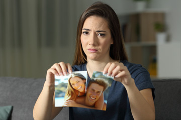 Sad woman looking at you breaking a photo after breakup