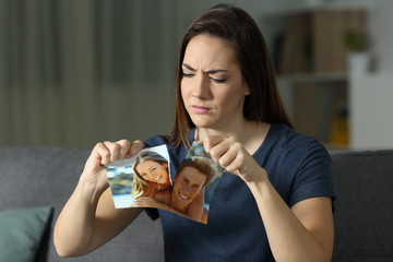 Angry girl breaking a couple photo after breakup