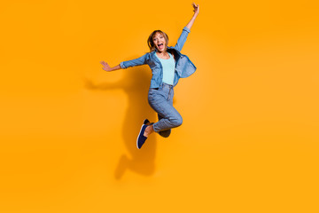 Full length body size photo jumping flight high amazing beautiful she her lady hands arms legs in win  raised up glad yell wearing casual jeans denim shirt clothes isolated on yellow background