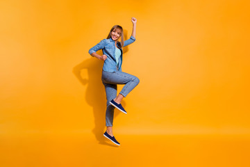 Full length body size photo jumping flight high amazing beautiful she her lady have walk hands arms legs in raised up glad wearing casual jeans denim shirt clothes isolated on yellow background