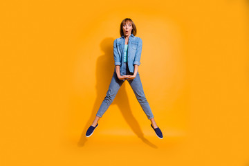 Wall Mural - Full length body size photo jumping flight high amazing beautiful she her lady unexpected prices shopping mall store wearing casual jeans denim shirt clothes isolated on yellow background