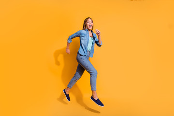 Wall Mural - Full length body size photo jumping flight high amazing beautiful she her lady unexpected prices rushing for shopping mall store wearing casual jeans denim shirt clothes isolated on yellow background