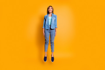 Wall Mural - Full length body size photo amazing toothy smiling in flight jumping high beautiful she lady legs hands arms together wearing casual jeans denim shirt clothes isolated on yellow background