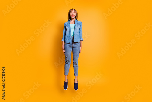 Wall mural Full length body size photo amazing toothy smiling in flight jumping high beautiful she lady legs hands arms together wearing casual jeans denim shirt clothes isolated on yellow background
