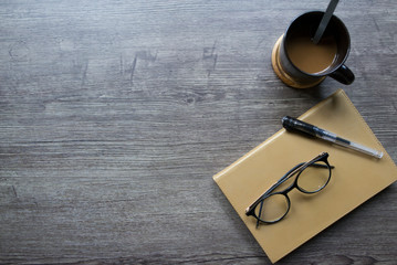 Notebook paper and glasses placed on wooden table. Copy space.